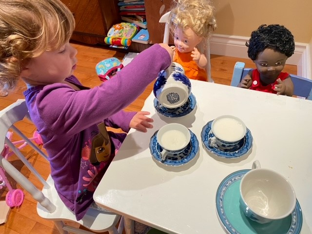 girl with dolls and tea set