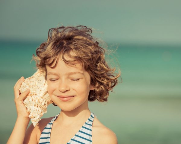 child listening to a seashell